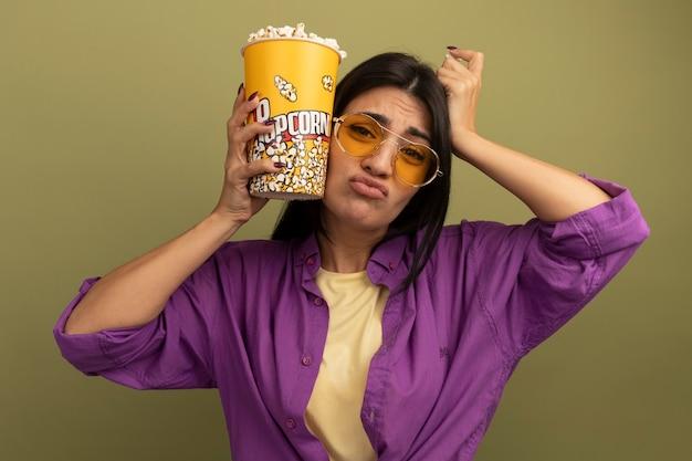 태양 안경에 불쾌한 예쁜 갈색 머리 백인 여자는 팝콘 양동이를 보유하고 올리브 그린에 머리에 손을 넣습니다