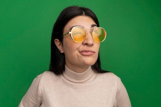 Ragazza caucasica abbastanza mora sgradita in occhiali da sole cerca sul verde