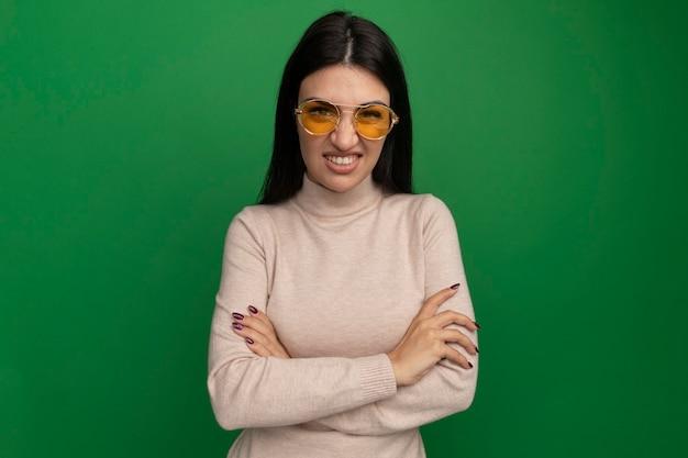 Ragazza caucasica abbastanza mora dispiaciuta in occhiali da sole in piedi con le braccia incrociate sul verde