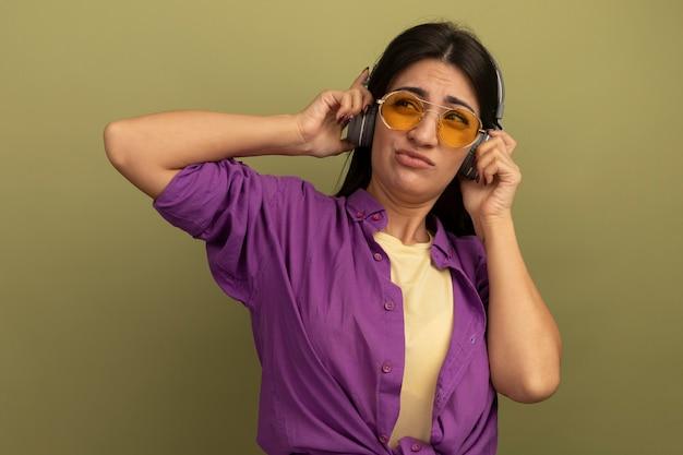 Ragazza caucasica abbastanza mora dispiaciuta in occhiali da sole con le cuffie guarda a lato su verde oliva
