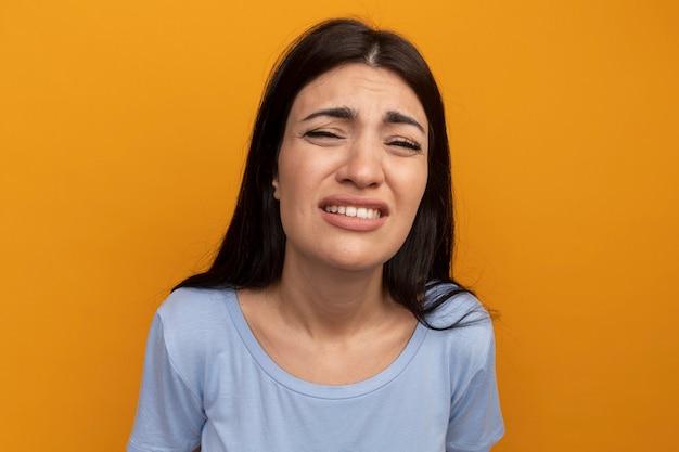 Donna graziosa del brunette dispiaciuta che esamina la parte anteriore isolata sulla parete arancione