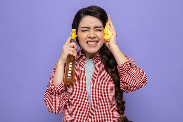 Una donna delle pulizie caucasica piuttosto spiacevole che tiene in mano panni per la pulizia e un detergente spray vicino alla sua testa