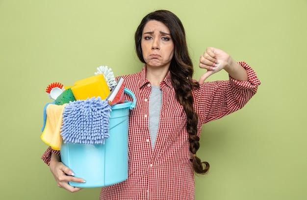Una donna delle pulizie caucasica piuttosto scontenta che tiene in mano l'attrezzatura per la pulizia e guarda verso il basso il pollice verso il basso