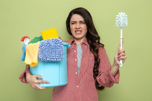 Donna delle pulizie piuttosto caucasica scontenta che tiene in mano attrezzature per la pulizia e scopino per wc