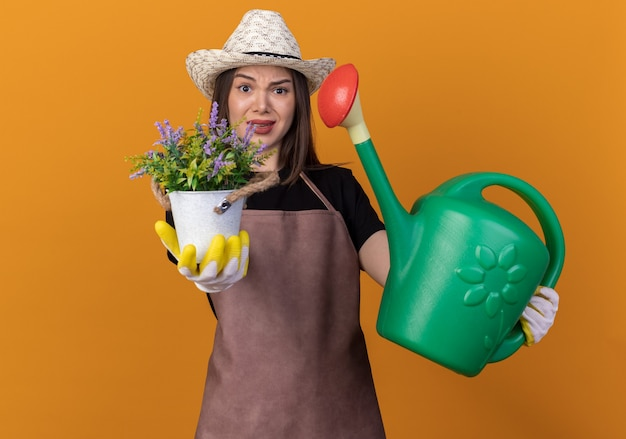 Unpleased pretty caucasian female gardener wearing gardening hat and gloves holding flowerpot and watering can