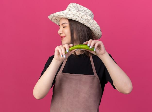 Недовольная красивая кавказская женщина-садовник в садовой шляпе держит острый перец