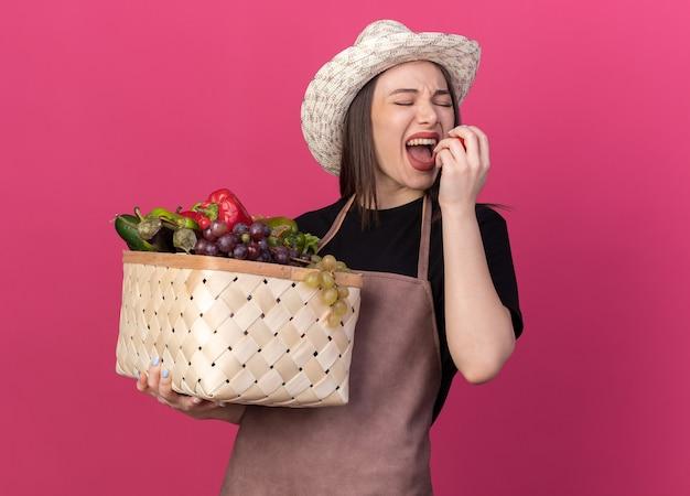 Una giardiniera caucasica scontenta che indossa un cappello da giardinaggio che tiene un cesto di verdure e fa finta di mordere il pomodoro