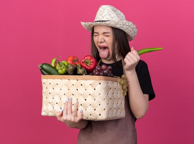 ガーデニング帽子をかぶった不機嫌なかなり白人女性の庭師は、野菜のバスケットと唐辛子を保持している舌を突き出します