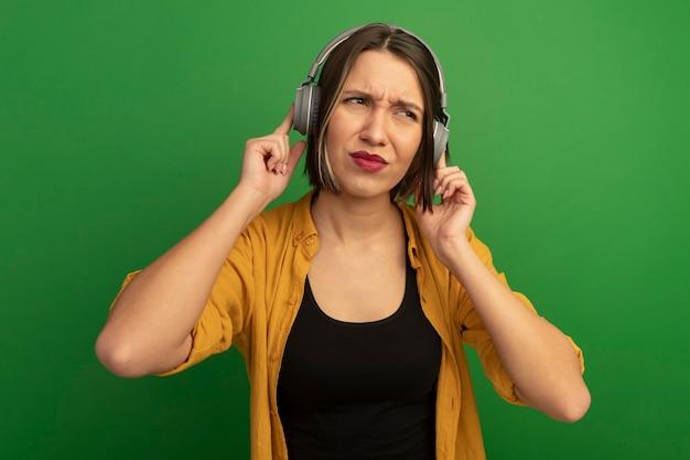 헤드폰에 불쾌 하 게 예쁜 백인 여자는 녹색 측면에서 보이는