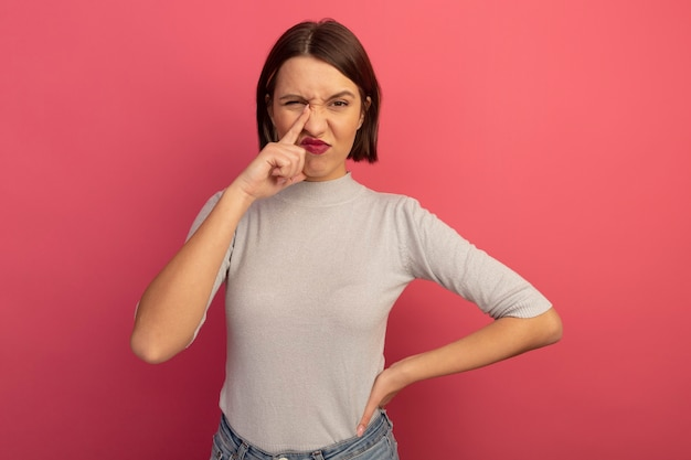 不機嫌なかなり白人女性はピンクの鼻に指を置きます