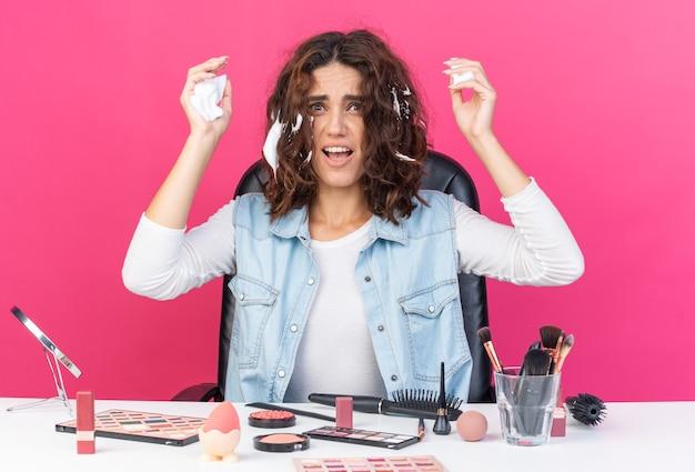 ヘアムースを適用する化粧ツールでテーブルに座っている不機嫌なかなり白人女性