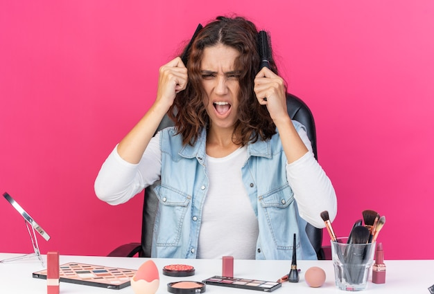 Unpleased pretty caucasian woman sitting at table with makeup tools combing her hair