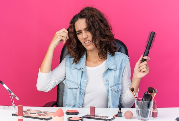 Unpleased pretty caucasian woman sitting at table with makeup tools holding comb and combing her hair