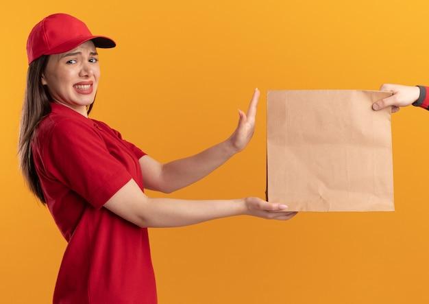제복을 입은 불쾌한 예쁜 배달 여성은 복사 공간이 있는 주황색 벽에 격리된 카메라를 보고 있는 누군가에게 종이 패키지를 제공합니다