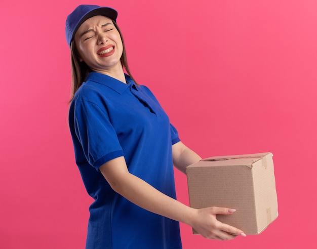 La donna graziosa delle consegne scontenta in uniforme tiene la scatola di cartone isolata sulla parete rosa con lo spazio della copia