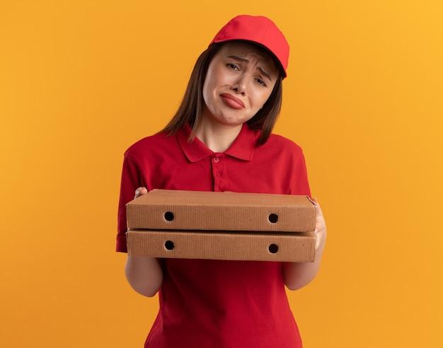La graziosa donna delle consegne scontenta in uniforme tiene le scatole della pizza