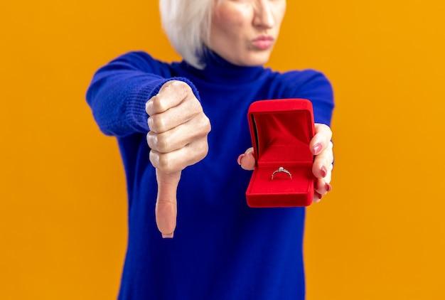 Una bella donna slava scontenta che tiene in mano una scatola di anelli rossi e fa il pollice verso il basso il giorno di san valentino