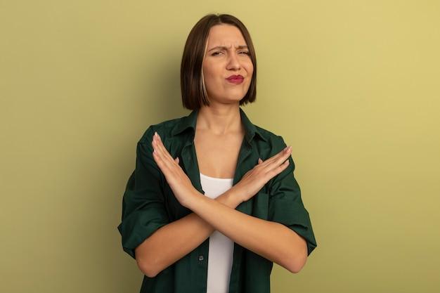 オリーブグリーンの壁に隔離された兆候を身振りで示す手を交差させる不機嫌なきれいな女性