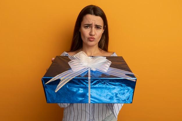 La donna graziosa insoddisfatta tiene il contenitore di regalo isolato sulla parete arancione