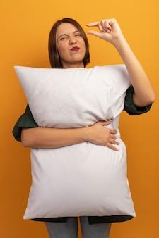 不機嫌なきれいな女性は枕を抱きしめ、オレンジ色の壁に隔離された何かを保持するふりをします