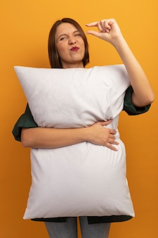 Unpleased pretty woman hugs pillow and pretends to hold something isolated on orange wall