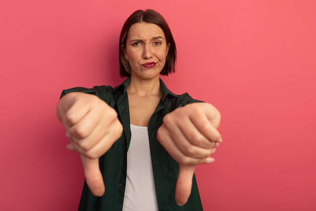 분홍색 벽에 고립 된 두 손으로 불쾌한 예쁜 여자 엄지 손가락