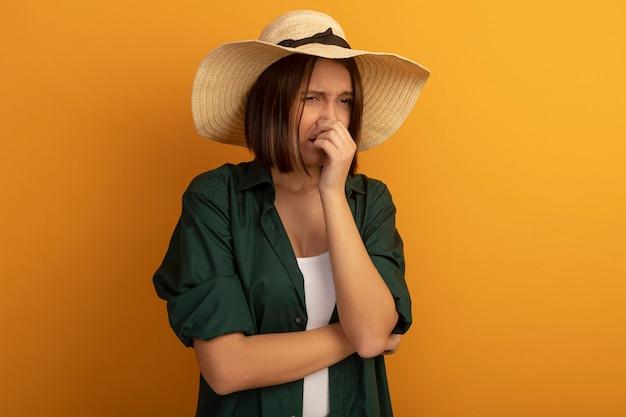 ビーチ帽子をかぶった不機嫌そうなきれいな女性は、オレンジ色の壁に隔離された鼻を閉じます