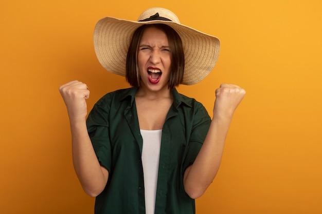 ビーチ帽子をかぶった不機嫌そうなきれいな女性は、オレンジ色の壁に拳を隔離し続けます