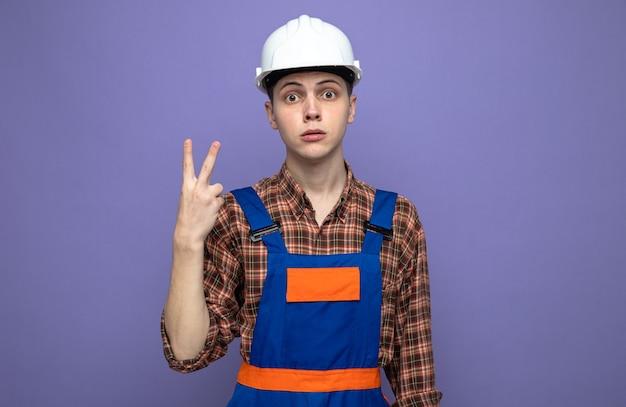 制服を着た若い男性ビルダーの平和ジェスチャーを見せて不満