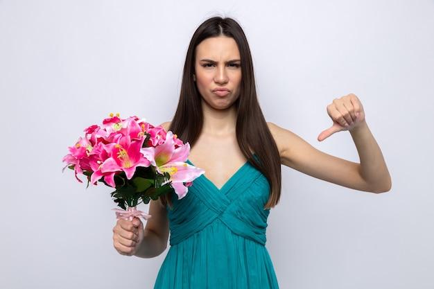 白い壁に分離された花束を保持している幸せな女性の日に美しい若い女の子を親指で示すのは不愉快です