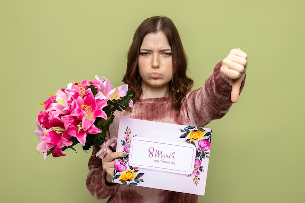 올리브 녹색 벽에 격리된 엽서와 함께 꽃다발을 들고 행복한 여성의 날에 아름다운 어린 소녀를 엄지손가락으로 아래로 보여주는 불쾌한