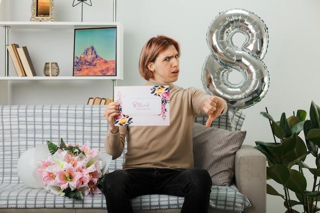 Dispiaciuto che mostra il pollice verso il bel ragazzo il giorno delle donne felici con in mano un biglietto di auguri seduto sul divano in soggiorno