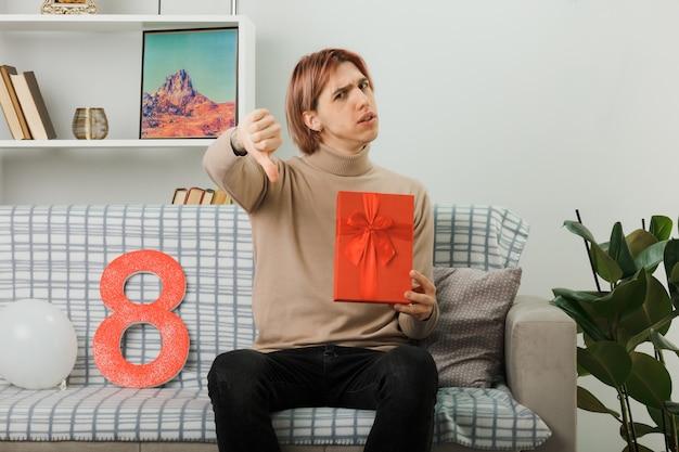 Недовольство показывает палец вниз красивого парня в счастливый женский день, держа в руках подарок, сидя на диване в гостиной