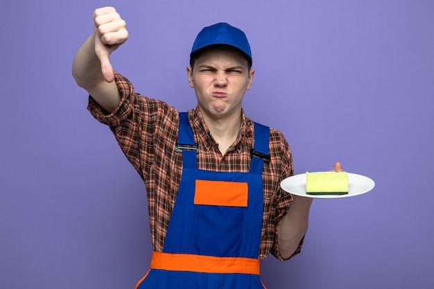Dispiaciuto che mostra il pollice verso il basso giovane addetto alle pulizie che indossa l'uniforme e il cappuccio che tiene la spugna sul piatto