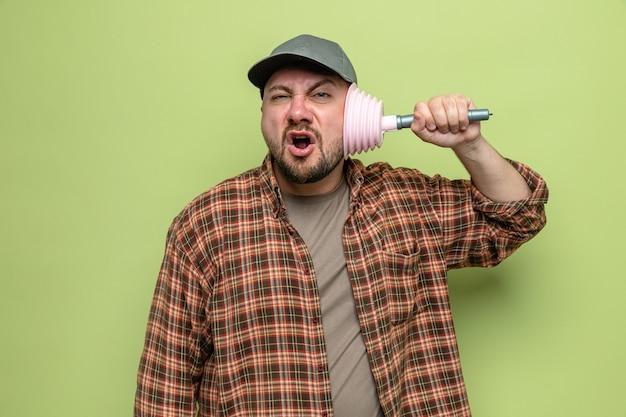 Uomo delle pulizie slavo scontento che si copre l'orecchio con uno stantuffo di gomma