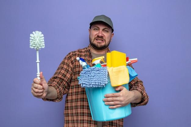 Pulitore slavo scontento che tiene in mano attrezzature per la pulizia e scopino per wc