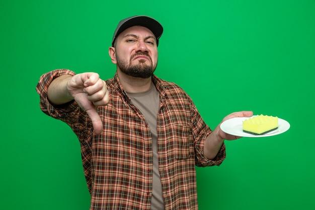Pulitore slavo scontento che tiene la spugna sul piatto e fa il pollice verso il basso