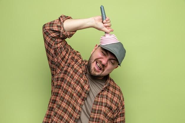 Uomo delle pulizie slavo scontento che mette uno stantuffo di gomma sulla sua testa