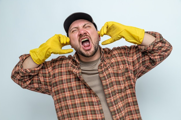 Unpleased slavic cleaner man with rubber gloves closing his ears with fingers