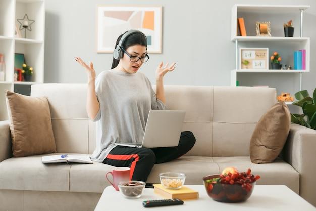 リビングルームのコーヒーテーブルの後ろのソファに座ってヘッドフォンを保持し、ラップトップを使用して眼鏡をかけている若い女の子が手を広げて不満