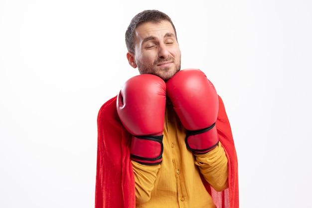 L'uomo del supereroe dispiaciuto tiene i guantoni da boxe sotto il mento isolato sul muro bianco