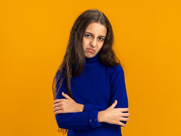 Недовольная девочка-подросток, стоящая в закрытой позе, глядя на фронт, изолированную на оранжевой стене с копией пространства