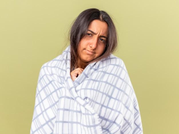 オリーブグリーンで隔離の格子縞に包まれた不機嫌な傾いた頭の若い病気の女の子