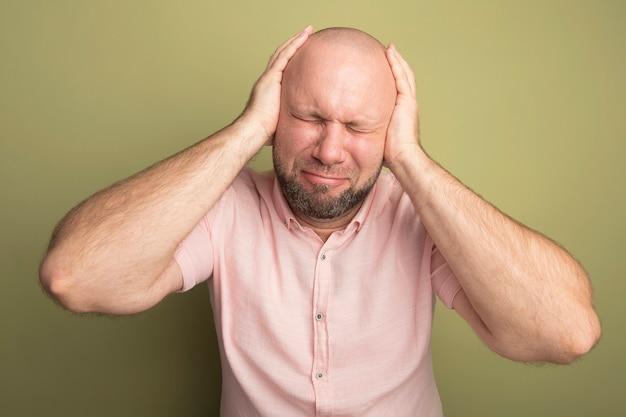 Insoddisfatto con gli occhi chiusi uomo calvo di mezza età che indossa la maglietta rosa che mette le mani sulle orecchie isolate su verde oliva