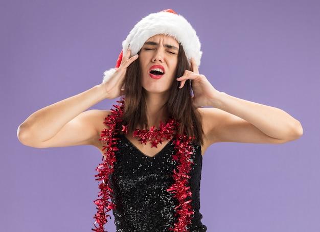 닫힌 된 눈으로 불쾌한 젊은 아름다운 소녀 보라색 배경에 고립 된 머리에 손을 넣어 목에 갈 랜드와 함께 크리스마스 모자를 쓰고 무료 사진