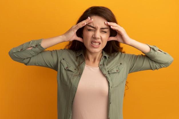 Недовольная закрытыми глазами молодая красивая девушка в оливково-зеленой футболке, положив руки на ноющий лоб, изолированный на желтой стене