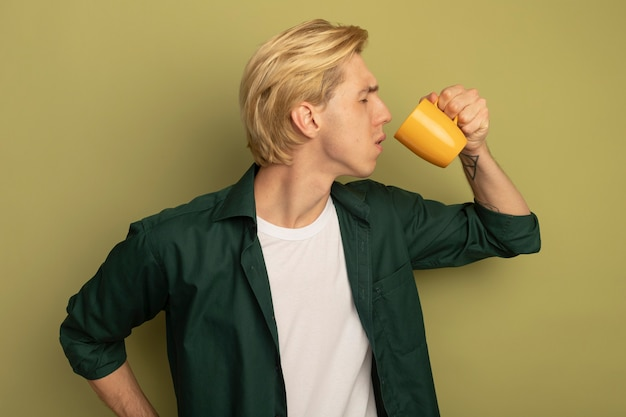 Unpleased with closed eyes young blonde guy wearing green t-shirt drinks tea