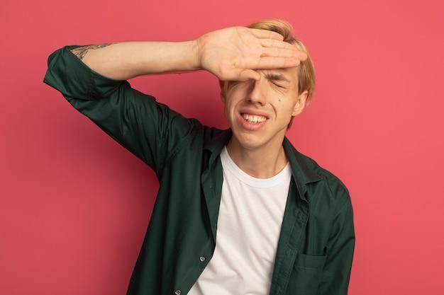 Недовольный закрытыми глазами молодой блондин в зеленой футболке, положив руку на лоб, изолированный на розовом