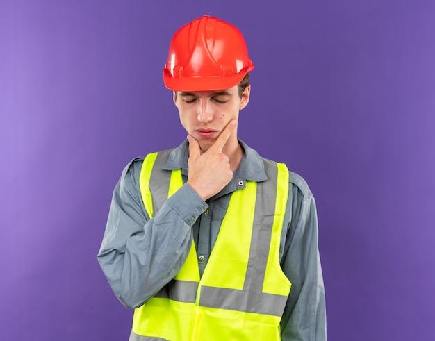 目を閉じて不機嫌な制服を着た若いビルダー男あごをつかんだ