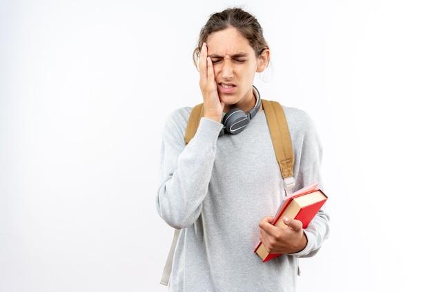 白い壁に隔離された痛む歯に手を置いて本を持って首にヘッドフォンでバックパックを身に着けている目を閉じて不満若い男の学生